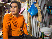 05 SEPTEMBER 2013 - BANGKOK, THAILAND:  A worker cuts relaxes in the makeshift hallway between corrugated metal dormitories that serve as worker housing at the construction site of a new high rise apartment / condominium building on Soi 22 Sukhumvit Rd in Bangkok. The workers live in the corrugated metal dorms on the site. Most of the workers at the site are Cambodian immigrants.             PHOTO BY JACK KURTZ