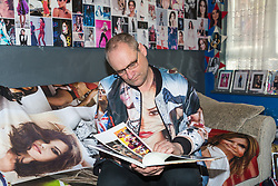 Shaun Smith, 52, from Basildon in Essex gazes at one of his many books of Cheryl Cole. He has built up a huge collection of Cheryl Cole memorabilia, including books, mugs, posters, signed photographs and as well as blankets, dressing gowns and other items he has had made, in the space of about eight months after she impressed him in a music video he was watching.. PLACE, January 24 2019.