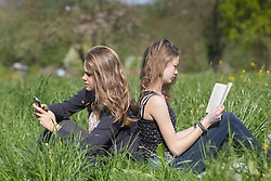 Teenage girls sitting in field, Freiburg im Breisgau, Baden-Wuerttemberg, Germany