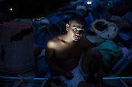 A Cambodian man sitting in front of a dump is partially illuminated by a flashlight, Cambodia, Southeast Asia