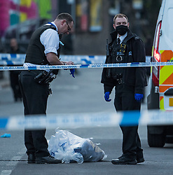 © Licensed to London News Pictures. 29/04/2021. London, UK. Police gather evidence at the scene at High Road in Willesden Green, North West London, where a man, reported to be in his 40s, has been stabbed to death at a bus stop. Photo credit: Ben Cawthra/LNP