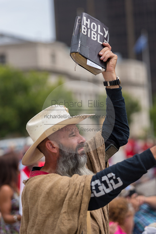 """An Evangelical Christian holds up a bible during the """"Stand With God"""" rally  August 29, 2015 in Columbia, SC. Thousands of conservative Christians gathered at the State House to rally against gay marriage and listen to GOP presidential candidates Gov. Rick Perry and Sen. Ted Cruz speak."""