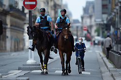 Mounted Police on horses on the bicycle path in front of a women on a bike wearing facemask on Rivoli Street in Paris on May 4, 2020, on the forty-ninth day of a strict lockdown in France, in place to attempt to stop the spread of the new coronavirus (COVID-19). Photo by Raphael Lafargue/ABACAPRESS.COM