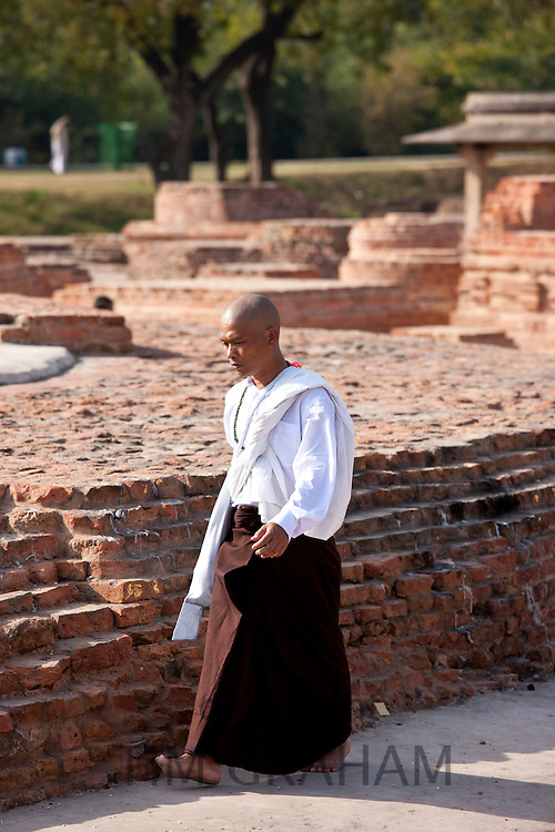 Buddhist monk praying as he walks around Dharmarajika Stupa at Sarnath ruins near Varanasi, Benares, Northern India