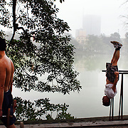 Men exercise at a make shift gym on a misty morning beside Hoan Kiem Lake, Hanoi, Vietnam.. For a county not know for it's sporting prowess, Hanoi, Vietnam's capital, appears to be gripped in a fitness frenzy. Before 6am street corners, parks and lake sides are a hive of activity as keep fit classes, Tai chi and personal exercise regimes are seen in abundance around the city. Particularly noticeable are Women's keep fit classes, often accompanied by loud poor quality western disco beat music as the occupants of the city get fit come rain or shine. Hanoi, Vietnam. 18th March 2012. Photo Tim Clayton