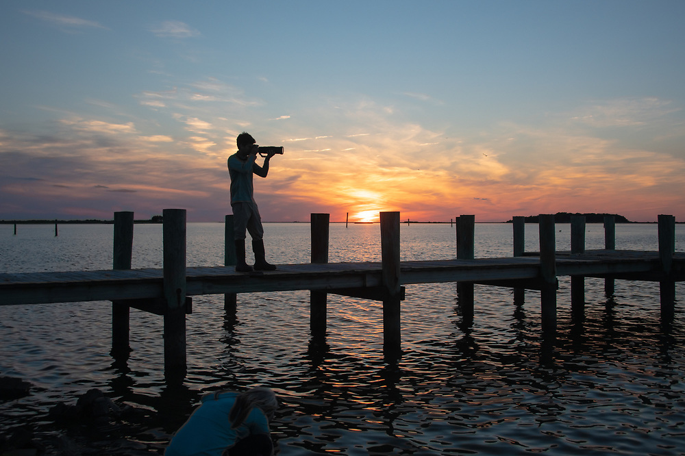 Silhouette of lone photographer on pier at sunset