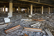 Looted department store next to central square. The floor is covered with decayed ceiling tiles and strip lights.