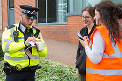 London, UK. 3 September, 2019. A Metropolitan Police officer carries out a stop and search on an activist attending the second day of a week-long carnival of resistance against DSEI, the world's largest arms fair, which is being hosted by ExCel London. The second day's events were organised around a theme of No Faith In War and were attended by representatives of many faith groups including a significant number of Quakers.