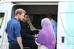 Prince Harry watches a demonstration of a rapid HIV test conducted in a mobile testing van before he attends an Action for Aids reception at Eden Hall in Singapore.