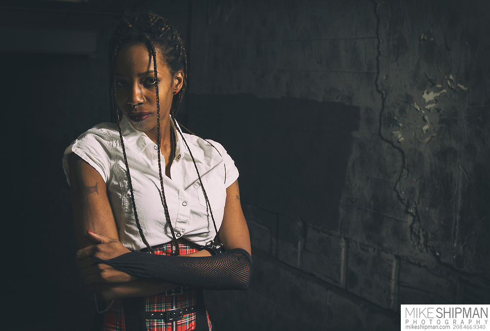 African American woman in white shirt and red corset with braided hair stands in a dark alleway