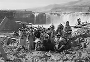 9305-B7362-1.  Indians in traditional dress at Celilo Falls. September 1938. 1= Louise Thompson. 2= Agnes Thompson. 3= either Margaret Buck or Roslene Yallup Napoleon (daughter of Hannah Yallup), 4= Hannah Sohappy Yallup (wife of Tom Frank Yallup), 5= ?child, 6= Pee-up-sun-yai (wife of William Yallup), 7= ?child, 8= Chief William Yallup, 9= ?child, 10= Henry Thompson, 11= ?child, 12= Tom Frank Yallup. Celilo Falls, Columbia River, Oregon