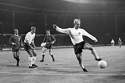 England's Bobby Charlton breaks clear to the apparent amazement of teammate Roger Hunt and to the despair of the Welsh defenders.