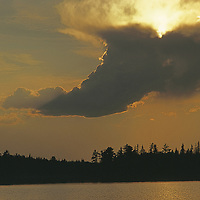 Sun behind thunderheads over white pine forests.