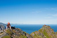 Hiker sits on mountain peak near Reinebringen, Moskenesoy, Lofoten islands, Norway
