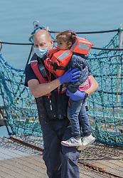 © Licensed to London News Pictures. 03/08/2021. Dover, UK. A young migrant is helped ashore by a Border Force officer at Dover Harbour in Kent after crossing the English Channel. Hundreds of migrants have made the crossing in recent weeks. Photo credit: Stuart Brock/LNP