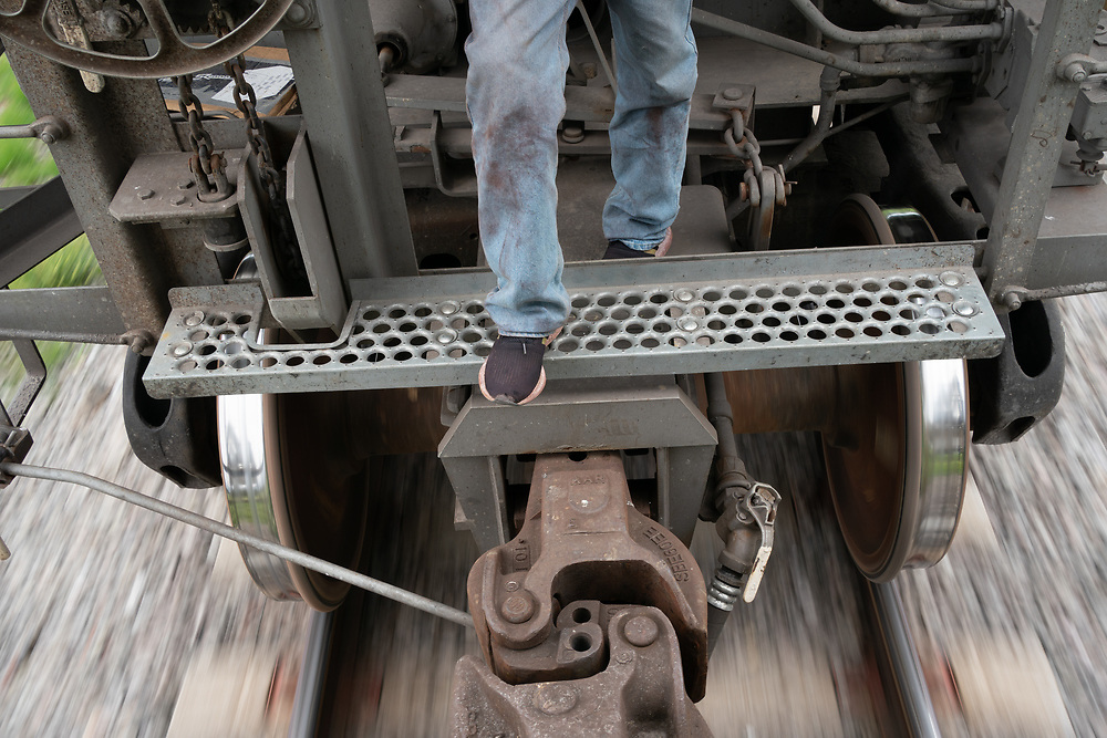 A Honduran migrant stands between carriages of a freight train on the Mexican rail network known as La Bestia or El Tren de la Muerte.