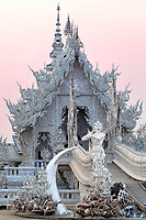 White Temple Sunset: Gremlins, soldiers and mystical guardians stand before the bridge that rises over the horror of hell on the path to Nirvana, Wat Rong Khun (the White Temple), Chiang Rai Thailand.    <br /> <br />                                   <br /> By Thai artist Chalermchai Kositpipat.