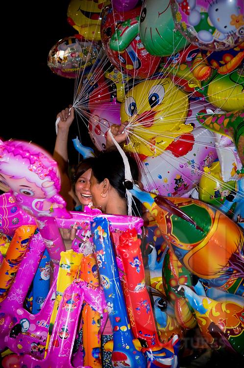 Street vendors sells balloon at night in a street of Hanoi, Vietnam, Southeast Asia