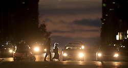 Pedestrians are silhouetted against the evening sky as they cross Franklin Street in Oakland, Calif., Monday, Jan. 25, 2016. (Photo by D. Ross Cameron)