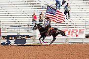 26 NOVEMBER 2011 - CHANDLER, AZ:    A woman on horseback carries the American flag into the arena during the opening ceremony at the Grand Canyon Pro Rodeo Association (GCPRA) Finals at Rawhide Western Town in west Chandler, AZ, about 20 miles from Phoenix Saturday. The GCPRA Finals is the last rodeo of the GCPRA season. The GCPRA is a professional rodeo association based in Arizona.     PHOTO BY JACK KURTZ