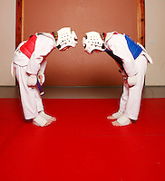 7 February 2008: 11 year old boy Ethan & Quinn Stafford bow to each other as opponets. Tae Kwon Do student athletes in motion. Young kids practicing Taekwondo at the USA Black Belt Academy in Huntington  Beach, CA. Tae Kwon Do is a Korean Martial Art discipline that trains the body and mind.  It is global sport that is an official Olympic sport. ? Background Retouched *
