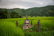 A stone cross shrine in a lush green paddy field flanked by hills and woods near Nongpoh, Ri-Bhoi district on 20th September 2018 in Meghalaya, India.