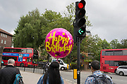 A young woman carries an oversized Happy Birthday balloon for a friend in Camberwell, on 30th May 2018, in London, England.