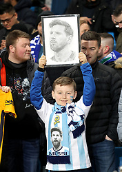 A young Argentina fan in the stands holds up a drawing of Lionel Messi during the international friendly match at the Eithad Stadium, Manchester.