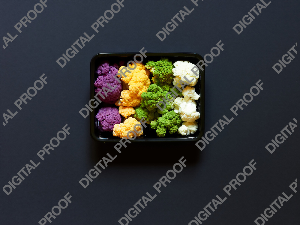 Set of seasonal and colorful cauliflower violet, yellow, green and white boxed in a plastic recipient  over a black background