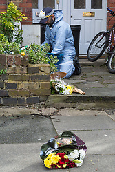 Floral tributes are blown onto the pavement as police go through the contents of rubbish bins as they continue to investigate at the the house where the body of French film producer 34-year-old Laureline Garcia-Bertaux was found buried in a shallow grave at an address in Kew, London, after she was reported missing on Tuesday march 5th 2019. London, March 10 2019.