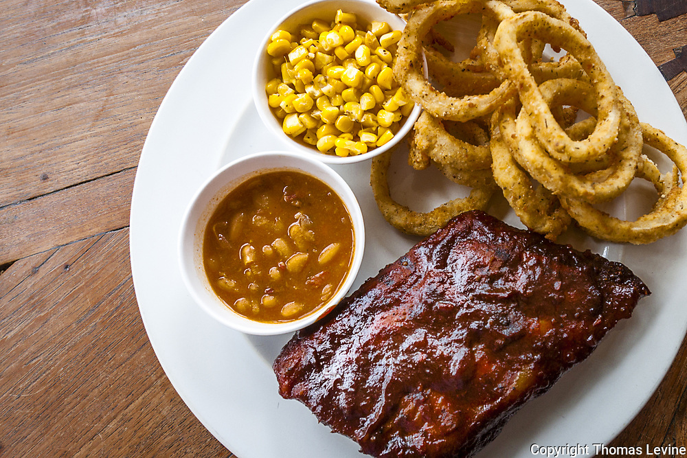 BBQ Ribs, baked beans, onion rings served on a white plate.