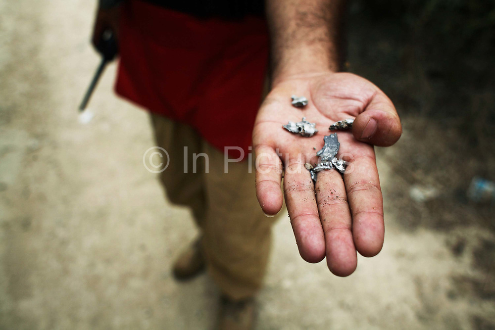 Small pieces of shrapnel from a deliberatly destroyed M85 cluster bomb unit in an olive grove in South Lebanon. The Danish Church Aid train local men and women to clear the huge number of cluster sub-munition left on the ground after the Israeli invasion and bombings in 2006.<br /> South Lebanon.