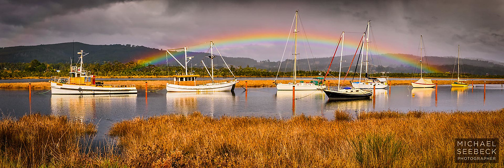 A rainbow appears behind boats on the Huon River as a shower passes over.<br /> <br /> Limited Edition Print; Edition of 125