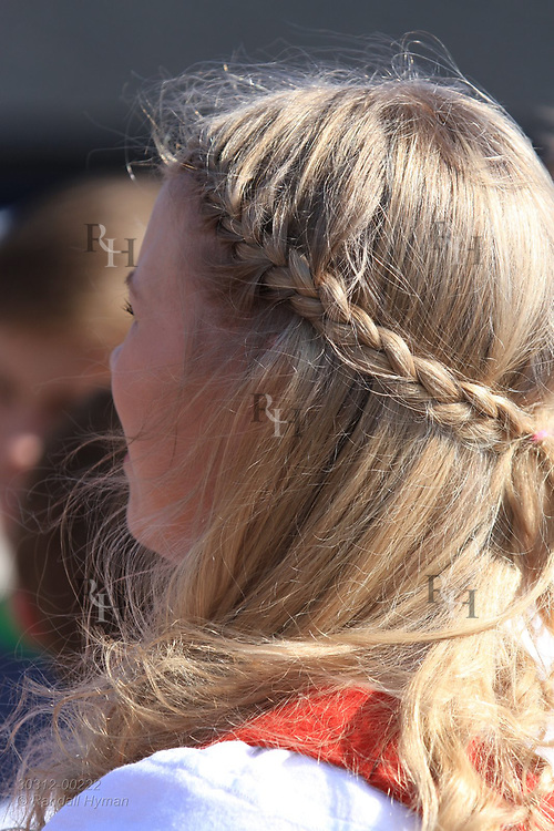 Blond girl wears finery for May 17th Constitution Day celebration of nation's independence in Kirkenes, Norway.