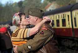 © Licensed to London News Pictures. 11/10/2014. Pickering, UK The annual wartime weekend in Pickering, North Yorkshire. People dress in 1940s period themed outfits and attend parades through the small Yorkshire town which has a traditional steam railway as would have been used in the 1940s. // Pictured: Lynda Anderson kisses goodbye to James Woods on Pickering station platform. Photo credit :  HARRY ATKINSON/LNP