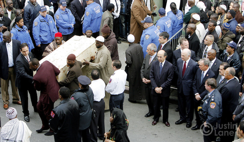 The coffin of one of the people killed in a recent house fire, which took 10 lives in total,  is carried into the Islamic Cultural Center in the Bronx, New York on Monday 12 March 2007. Of the ten people killed in the fire, 9 were children, and all were immigrants from Mali. Fourth from bottom right is New York Mayor Michael Bloomberg.