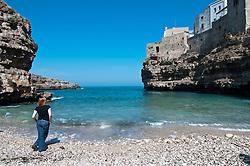 Polignano a Mare  è un comune italiano di 17.797 abitanti della provincia di Bari, in Puglia. Il nucleo più antico della cittadina sorge su uno sperone roccioso a strapiombo sul mare Adriatico a 33 chilometri a sud del capoluogo. L'economia del paese è essenzialmente basata sul turismo, l'agricoltura e la pesca..Di notevole interesse naturalistico sono le sue grotte marine e storicamente importanti sono il centro storico e i resti della dominazione romana. Tra questi ultimi il ponte della via Traiana, tuttora percorribile, che attraversa Lama Monachile..Dal 2008, Polignano a Mare ha sempre ricevuto la Bandiera Blu, riconoscimento conferito dalla Foundation for Environmental Education alle località costiere europee che soddisfano criteri di qualità relativi a parametri delle acque di balneazione e al servizio offerto in relazione a parametri quali la pulizia delle spiagge e gli approdi turistici. .La chiesa Matrice intitolata a Santa Maria Assunta e affacciata sulla piccola piazza Vittorio Emanuele, cuore del centro storico, fu cattedrale fino al 1818, quando la piccola diocesi di Polignano fu aggregata a quella di Monopoli. All'interno sono custodite alcune opere attribuite allo scultore Stefano da Putignano, attivo tra il XVI e il XVII secolo, e l'importante Polittico della Madonna con Bambino e Santi, del XV secolo su tavola dorata di Bartolomeo Vivarini restaurato nel 2007 a cura dell'ARPAI, oltre ad una moltitudine di altre piccole opere ed a preziosi paramenti sacri donati dall'ex Monastero di San Benedetto, oggi inesistente..Nella frazione di San Vito, sulla costa a nord del paese, proprio a ridosso del porticciolo si staglia l'imponente complesso dell'abbazia dei Benedettini. (fonte Wikipedia)