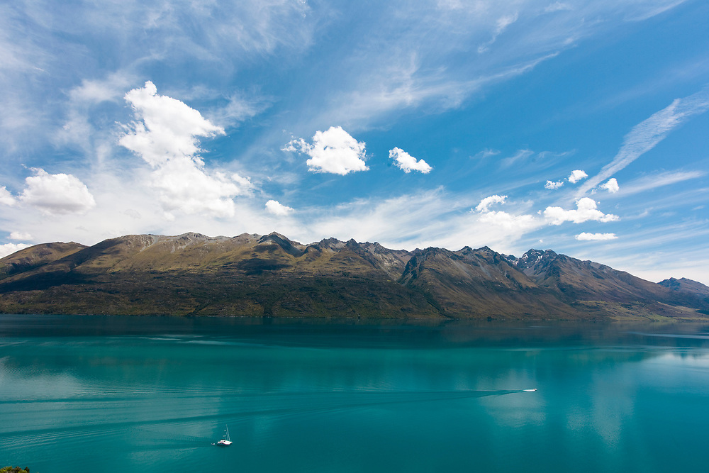 The acqua coloured water of Lake Wakatipu, Queenstown on sunny blue day