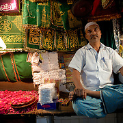 """A shop keeper selling souvenirs and offerings to the pilgrims at Nizamuddin Dargah, the mausoleum of Delhi's most famous Sufi saint Nizamuddin Auliya. It is visited daily by many people of all religions. The tomb of Amir Khusro is also located within the Nizamuddin Dargah Complex..The neighborhood of Delhi where the mausoleum is located is called """"Hazrat Nizamuddin"""" or simply """"Nizamuddin"""" because of this."""