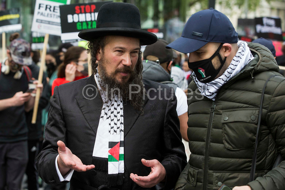 An ultra-Orthodox anti-Zionist Haredi Jew from Neturei Karta UK talks to a man wearing a Palestinian keffiyeh during the National Demonstration for Palestine on 22nd May 2021 in London, United Kingdom. The demonstration was organised by pro-Palestinian solidarity groups in protest against Israels recent attacks on Gaza, its incursions at the Al-Aqsa mosque and its attempts to forcibly displace Palestinian families from the Sheikh Jarrah neighbourhood of East Jerusalem.