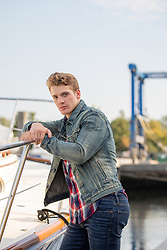 hot blond man in a denim jacket by a boat