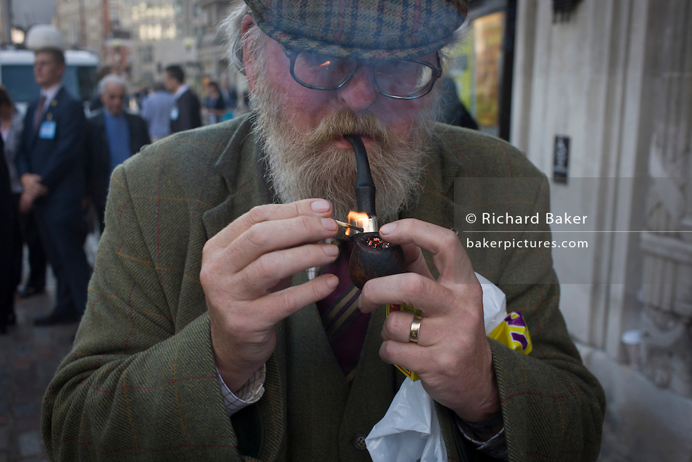 A man in his seventies lights his pipe in a central London street.