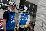 Paul Robertson, (left) a banker from Canada, and Ted Hunter (right) who works in marketing and is from the United States work as Peace Boat volunteers and take part in the clean-up operations in Ishinomaki, Miyagi Friday May 6th 2011. Around 350 volunteers took part in the relief effort over the Golden Week holiday, including 41 foreigners, clearing mud and removing debris from this coastal town which more almost levelled in the March 11th earthquake and tsunami.