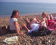 AYBR71 Woman friends and children sunbathe and chat on shingle beach summer England