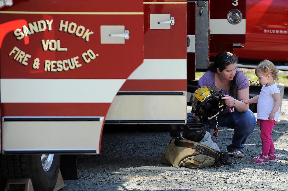 "Heather Schwartz of Sandy Hook, Conn., shows her daughter Jocelyn Schwartz a fireman's helmet as they tour a Sandy Hook Volunteer Fire Department truck during the town's ""Spring Fling Block Party"" in Newtown, Conn., Saturday, April 27, 2013.  (AP Photo/Jessica Hill)"
