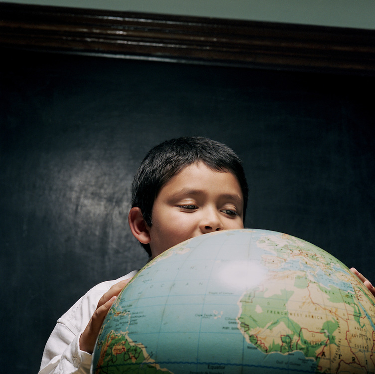 Boy, age 5-8 looking at a globe in a classroom in front of chalkboard