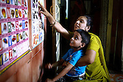 Teacher Usha Tilwana, 39, is assisting Arman Parwez, 6, a young boy suffering from a neurological disorder inside the Chingari Rehabilitation Centre in Bhopal, Madhya Pradesh, India, near the abandoned Union Carbide (now DOW Chemical) industrial complex Copyright: Alex Masi