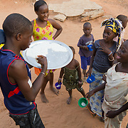 During the evening before Islamic New Year, Koumbadiouma's children go from compound to compound, receiving sugary treats. Kolda, Senegal.
