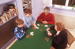 Family group with three generations playing game of cards,