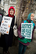 Whitehall November 28th Protest organised by Stop the War against the proposed bombing of Syria. A woman wearing a red hoodie holds a home-made plaacard saying 'Don't add fuel to the fire' and her friend holds one saying 'Justice and Peace in the Middle East'.